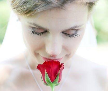 Bruid met een roos in haar hand, ze ruikt aan de roos