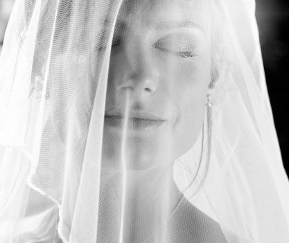 Bruid met ogen dicht en de sluier over haar gezicht, deze schijnt door waardoor je haar gezicht nog heel mooi ziet