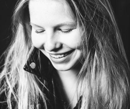 Kinderportret van een knap meisje met blond haar die schuin naar beneden kijkt, zwart wit foto