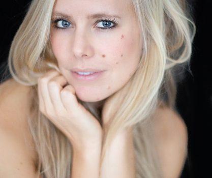 modellenfoto van een naakt model waar je alleen haar armen en schouders ziet, alles is verder bedekt met blond haar, pure foto, ze kijkt in de camera