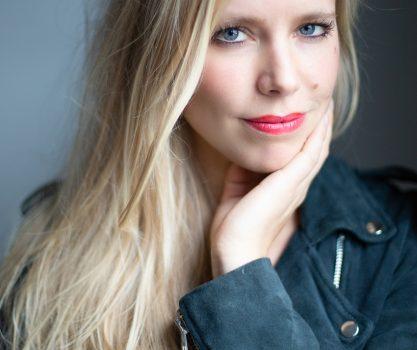 Modellen foto van blonde dame met een leren jasje en rode lippenstift, licht valt op haar gezicht
