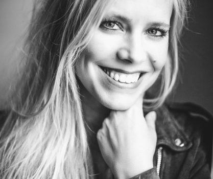 Blond model die lacht in de camera met prachtige ogen en witte tanden