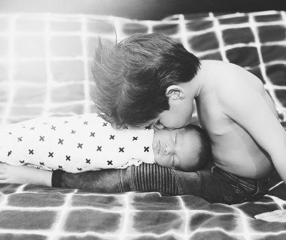Newbronfotografie van een baby tussen de 8 en 14 dagen oud, pure, lichte fotografie, oog voor details, zwart wit foto van een grote broer met zijn nieuwe kleine broertje
